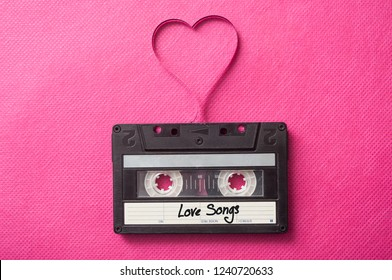 """closeup of audio cassette with text """"Love songs"""" with magnetic band in shaped heart on pink background"""