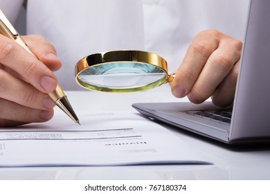 Close-up Of Auditor Inspecting Financial Documents At Desk