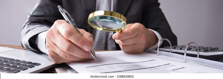 Close-up Of A Auditor's Hand Looking At Receipts Through Magnifying Glass At Workplace
