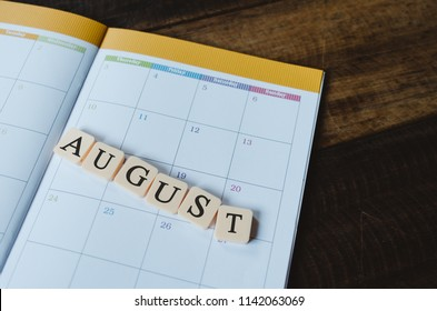 closeup of AUGUST text tile on planner book calendar on wooden table . Planning and AUGUST month concept