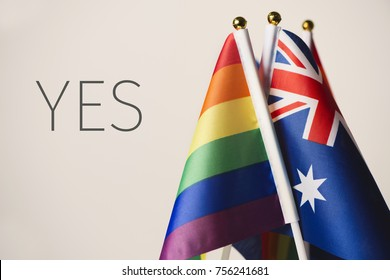 closeup of an australian flag and some rainbow flags, and the word yes, depicting the support to the same-sex union in Australia, against an off-white background