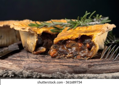 Closeup Australian meat pie on the wooden table with copy space, rustic style