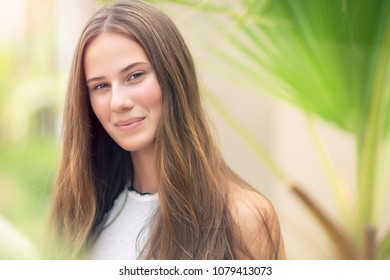 Closeup authentic portrait of a nice female in the park, fresh natural appearance of youthful girl, happy lifestyle of young people
