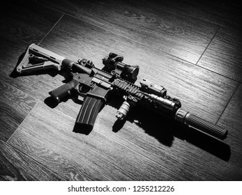 Close-up of automatic carbine on wooden floor in black and white