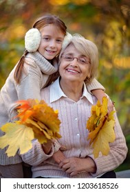 Closeup autumn portrait of happy grandmother with granddaughter outdoors.