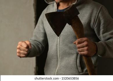 Close-up of the axe in the man's hand. The man with the axe