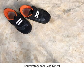 Closeup baby black shoes on polished concrete floor background and space