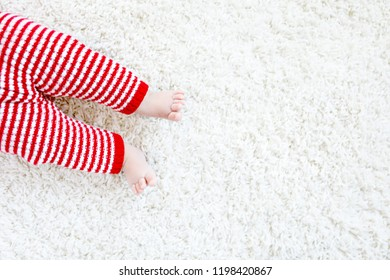 Close-up of baby body and legs in red Santa Clause trousers on Christmas