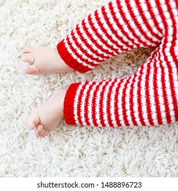Close-up of baby body and legs in red Santa Clause trousers. New born child, little girl or boy. Kid having fun. Family, new life, childhood, holiday concept. Closeup for Christmas postcard.