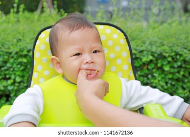 Close-up baby boy sitting on kid chair eating with something stuck in his mouth and mother help to keep out.
