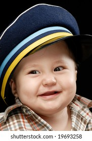 Close-up of a baby in checkered shirt and sailor's cap