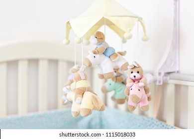 Close-up baby crib with musical animal mobile at nursery room. Hanged developing toy with plush fluffy animals. Happy parenting and childhood, expectation delivery of a child concept