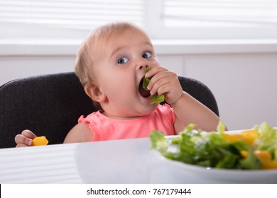 Close-up Of A Baby Girl Eating Healthy Food At Breakfast
