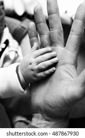 Close-up of baby holding his father's fingers and hands.