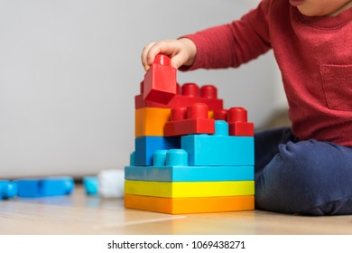 Closeup of a baby playing with colorful plastic bricks, selective focus.