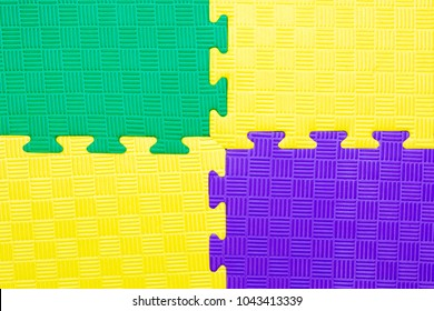 Close-up of baby playing mat background.  Jigsaw soft rubber surface texture. Foam floor children mat connection