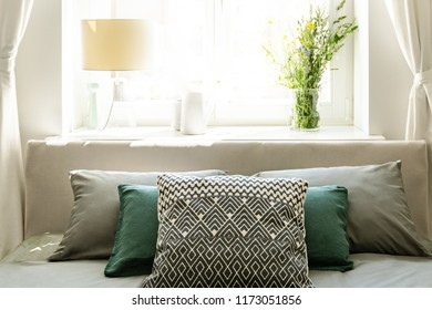 Close-up of the back of the bed with gray and green pillows against a sunny window with a lamp and a bunch of wild flowers on the windowsill in a natural bedroom interior. Real photo.