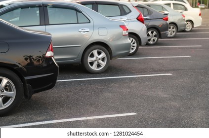 Closeup of back or rear side of black car with  other cars parking in parking area with natural background in the evening of sunny day. The mean of simply transportation in modern world.