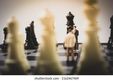 Closeup back view of miniature businessman on chess board.