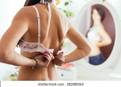 Closeup back view of a woman unhooking the clasp of her white bra and looking in the mirror
