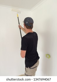 Closeup of the back of a young man wearing a black shirt and work shorts with a long extendable paint roller painting an interior wall white inside a house renovation in Australia