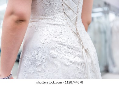Closeup back of young woman trying on lace corset wedding dress in boutique discount store, fitness watch