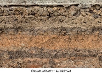 Close-up background image, cut section, gravel layer and mud under the concrete road, which was excavated to embed the pipe.