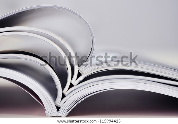 Closeup background of a pile of old magazines with bending pages. Small shallow dof.