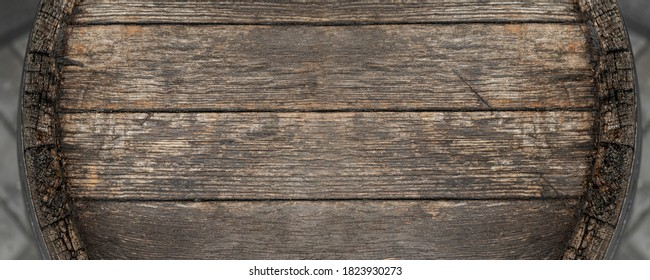 Close-up background of top of old retro vintage weathered wooden cask barrel. Wineyard, distillery, pub or bar table decoration design. Copyspace abstract natural flat lay surface. Panoramic banner