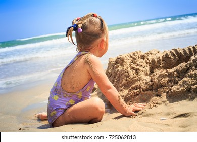 closeup backside view little blonde girl with pigtails sits on sand beach against long foamy ocean waves