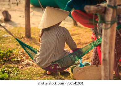 closeup backside view Vietnamese woman in national straw hat sits in small hammock in backyard