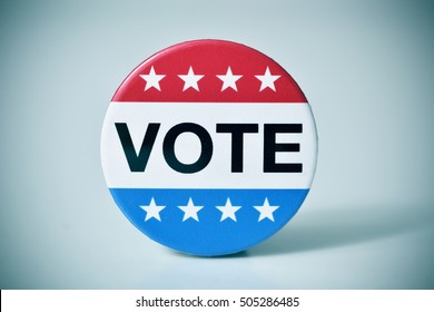 closeup of a badge with the word vote written in it, for the United States election, with a slight vignette added