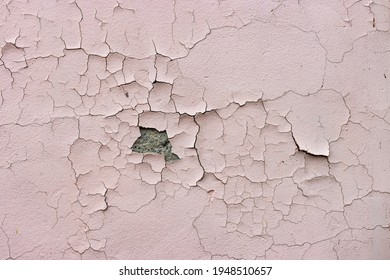 Close-up. Badly fixed building facade wall covered with cracks in stucco and paint. A big patch of stucco missing in the middle exposing the cement coat brown coat, rest is cracked and peeling. - Shutterstock ID 1948510657