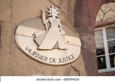 """closeup bailiff plate on french building facade - """"huissier de justice"""" ( text in french) bailiff"""