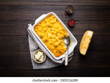 Close-up of baked mac and cheese in white casserole on rustic wooden background, with seasonings, butter, spoon and fork, top view. Pasta with cheesy sauce, American/English comfort food