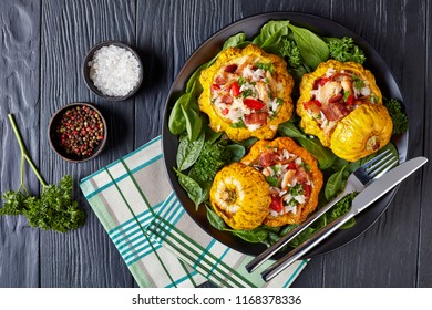 close-up of  baked Pattypan squash stuffed with rice, fried chicken meat, crispy fried bacon, red bell pepper and served with spinach leaves and parsley on a black plate with fork and knife