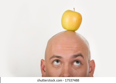 Close-up of bald male head with yellow apple on it
