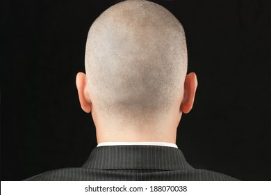 Close-up of a bald suited man, shot from behind.
