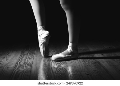 Closeup of a ballerina's feet in pointe shoes on a vintage, wood floor with black background. Black and white image with drama. One foot is pointed and the other is flat.