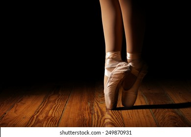 Closeup of a ballerina's feet in pointe shoes on a vintage, wood floor with black background.