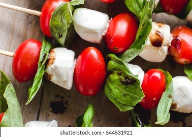 Close-up of balsamic drizzled-fresh caprese kabobs with tomatoes, fresh basil and mozzarella on light wooden surface.