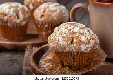 Closeup of a banana nut muffin and coffee mug on a wooden plate with muffins in background