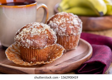 Closeup of banana nut muffins and cup of coffee on a wooden plate with  bananas in background