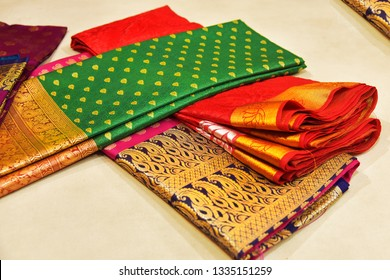 Closeup of Banares silk saris in a textile shop,  displayed in front of customers. These exquisite, expensive sarees are famous for their gold and silver zari, brocade.