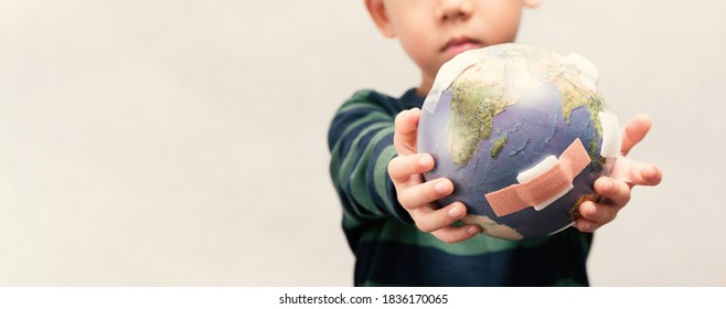 Closeup banner of cute little asian boy as a new generation holding and show damage globe full of bandages. Global warming, Climate change, Environmental problems. World pollution, Pandemic, Earth Day