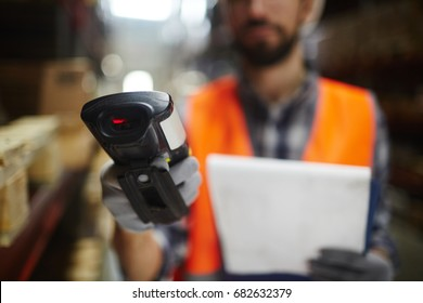 Closeup of bar code scanner in hand of unrecognizable warehouse worker doing inventory of stock