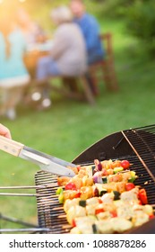 close-up of a barbecue where chicken skewers are cooking, friends gathered around a table to share a meal.