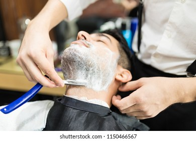 Closeup of barber hands shaving man's stubble with straight razors at shop