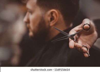Close-up of barber holds clip-on hair clipper barbershop
