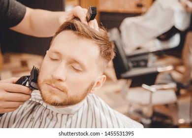 Close-up of barber shaving beard to man in barbershop.